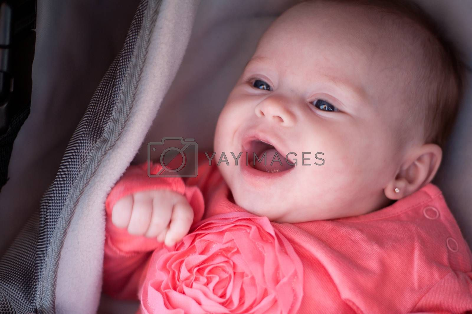 Happy baby is smiling in her pram