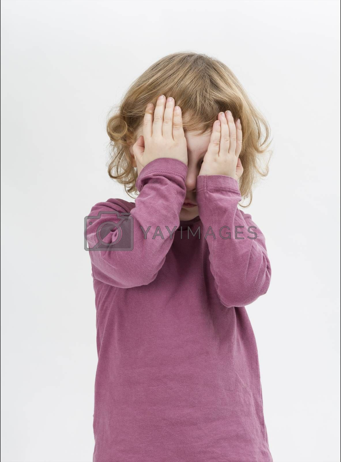 child covering eyes with hands. studio shot in grey background