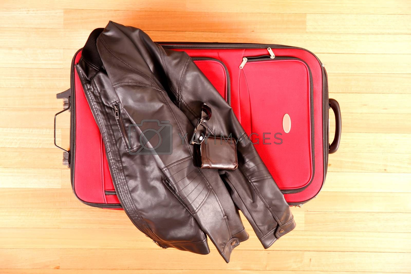 Ready to travel. A suitcase with glasses, wallet and a leather jacket.