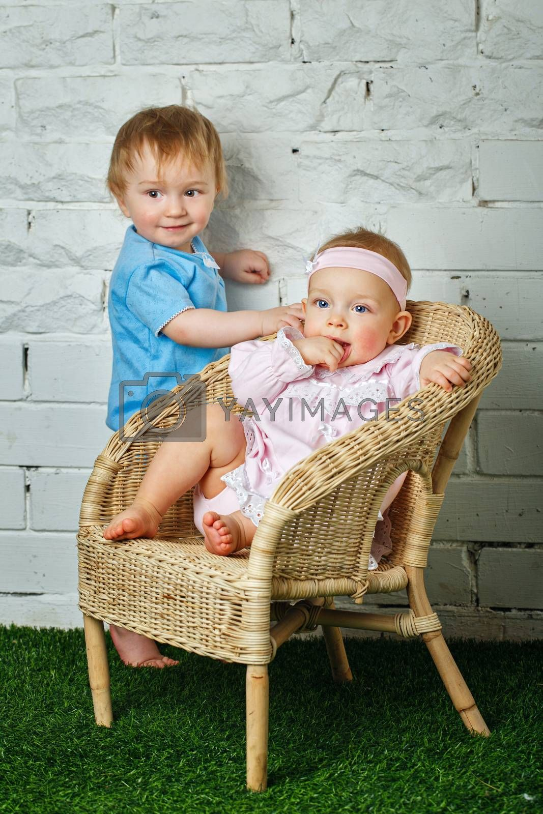 Brother and sister playing in the backyard next to the wicker chair