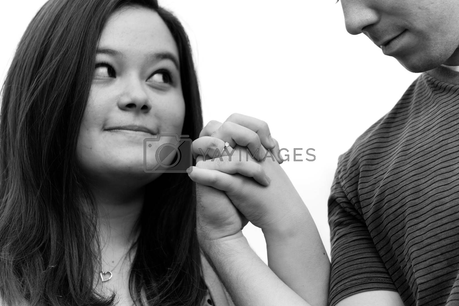 Young couple holding hands and showing the diamond engagement ring.  Shallow depth of field with sharpest focus on the ring.
