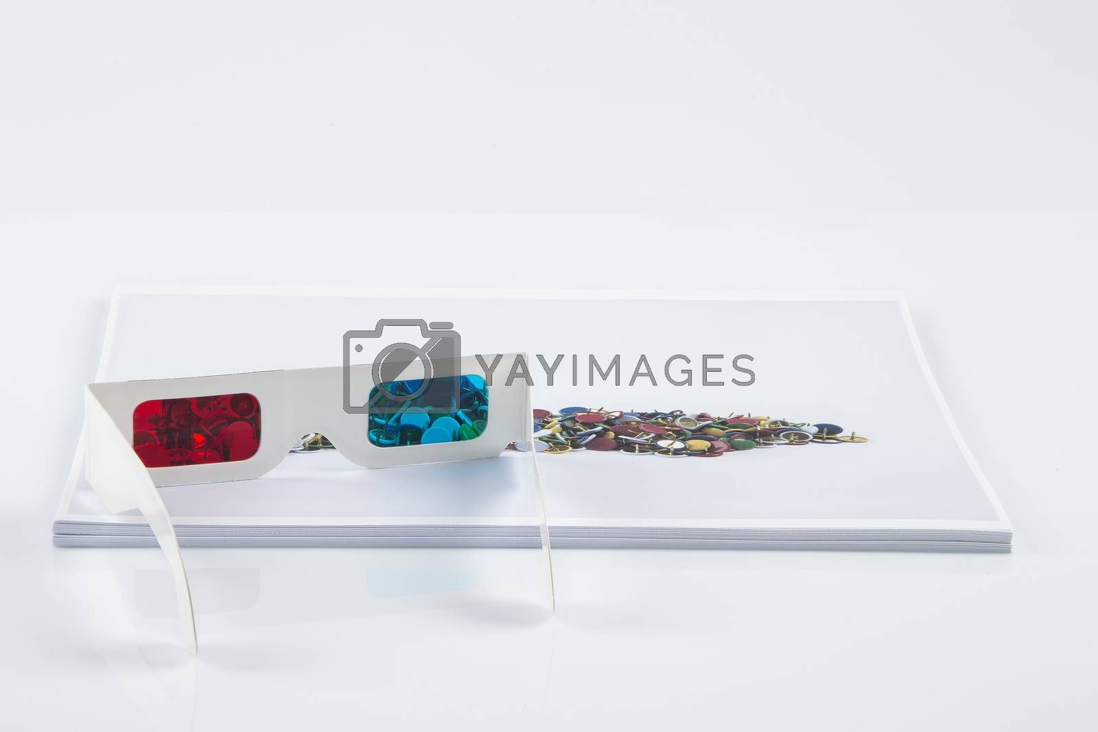 Royalty free image of 3D Print: white 3D anaglyphic Red Blue glasses and paper printed pins by paocasa