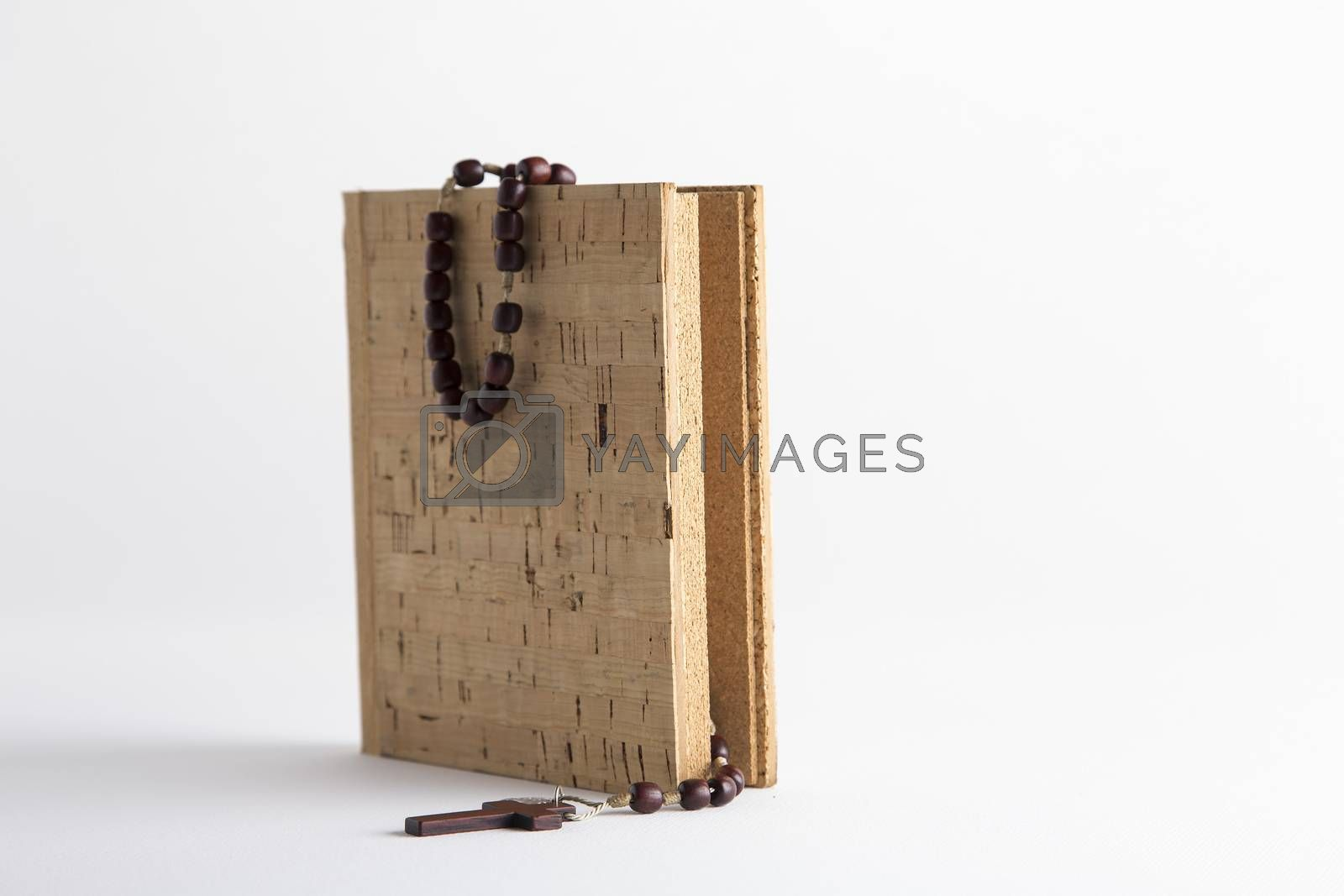 Rosary beads necklace on blank cork book