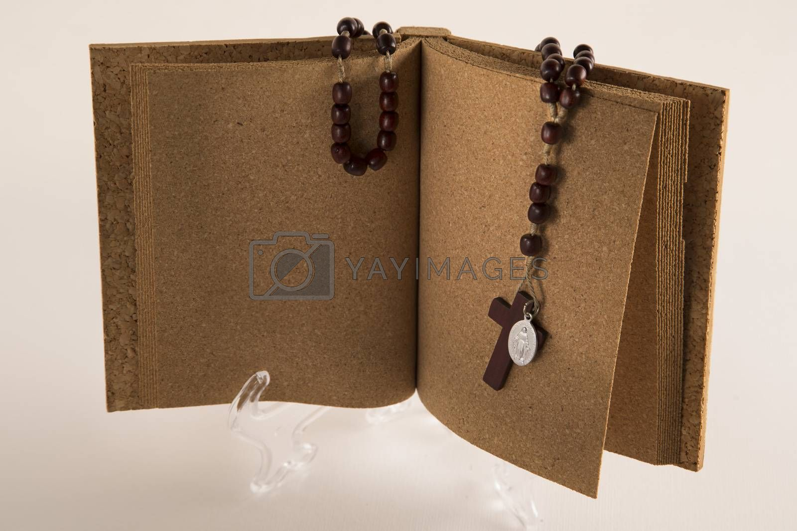 Holy Rosary beads necklace on cork book