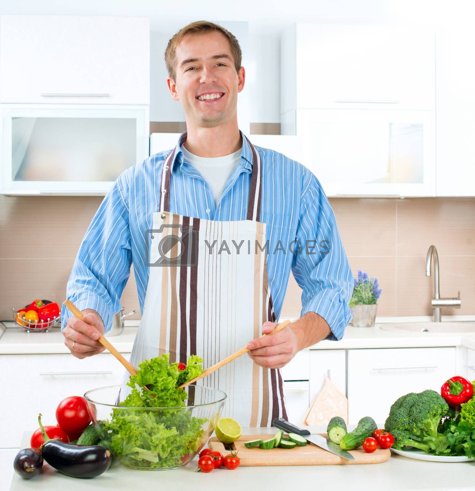 Royalty free image of Young Man Cooking. Healthy Food - Vegetable Salad by SubbotinaA