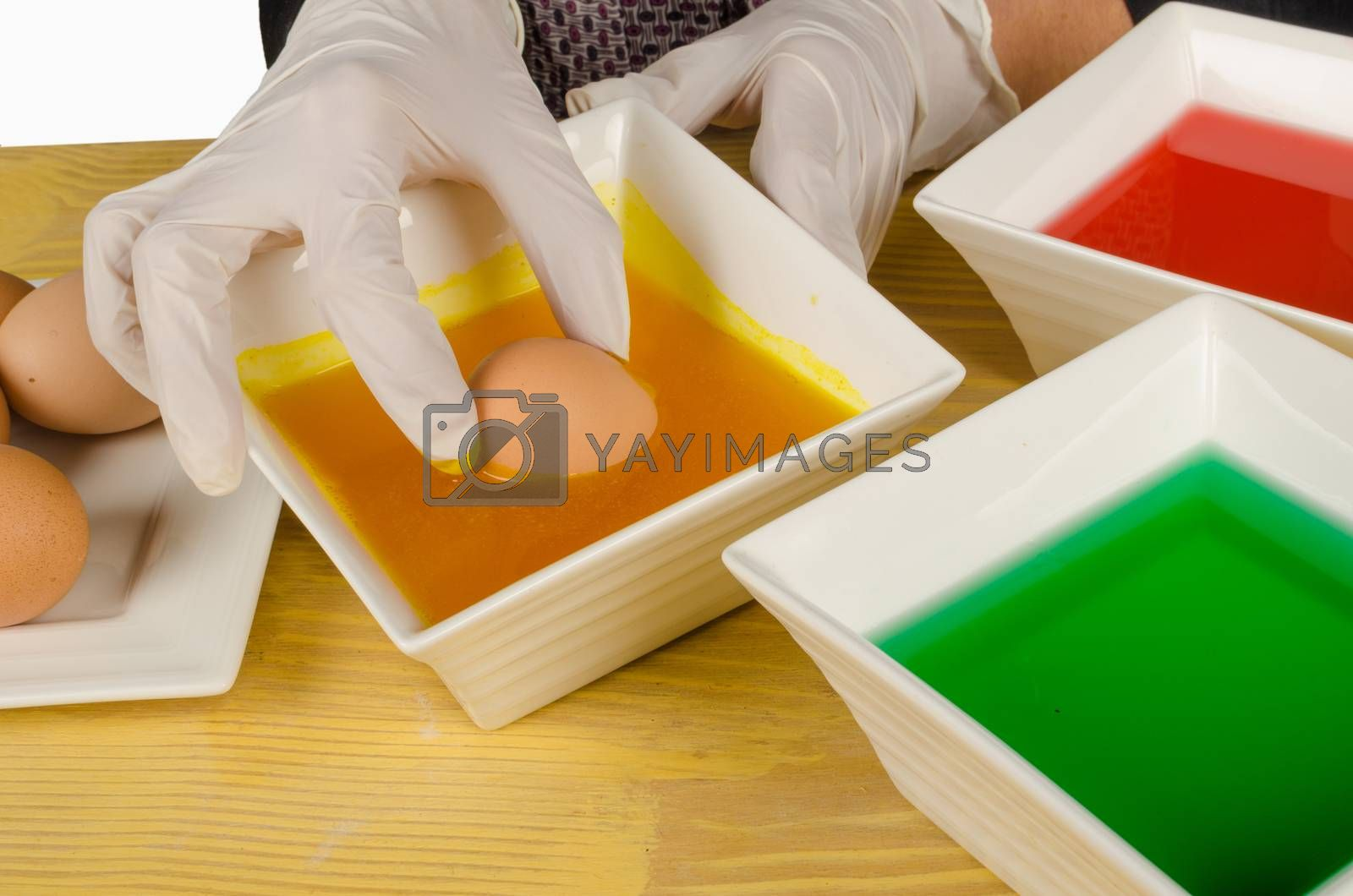 Royalty free image of Dipping Easter eggs by hemeroskopion