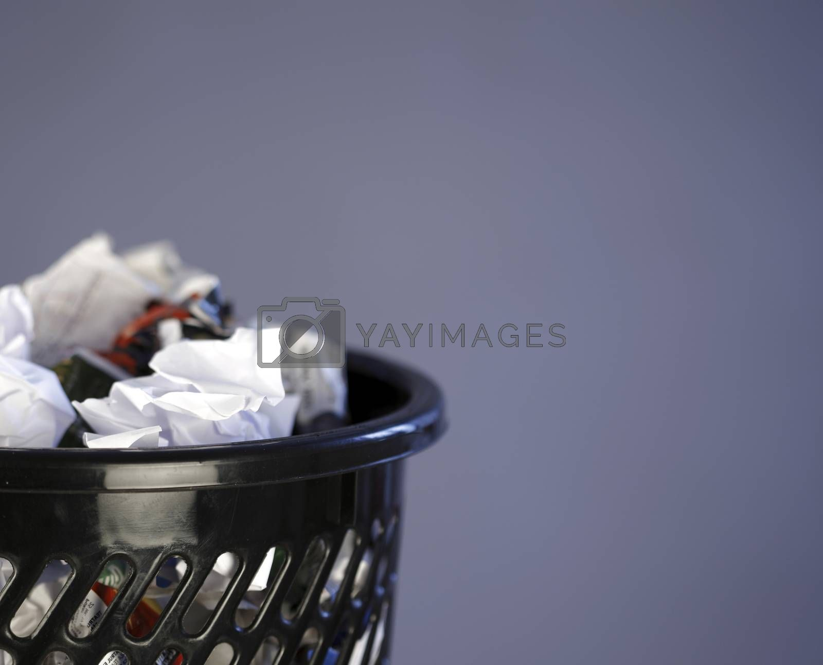 Close up photo of a trash can full of papers