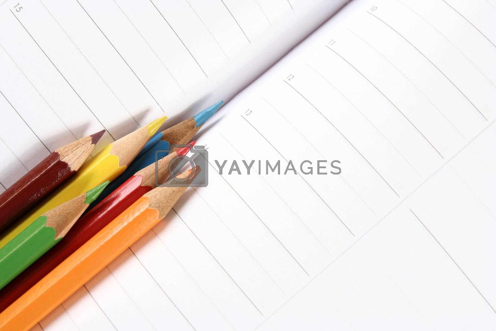 Close-up of color pencils and agenda