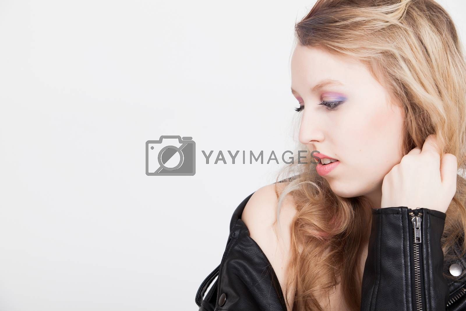 Young tough blond teenage girl with leather jacket on a white background