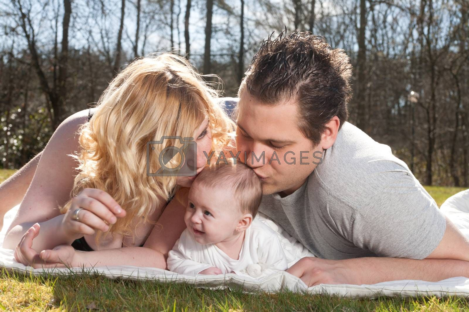Young family is having  nice time with their baby on a sunny day
