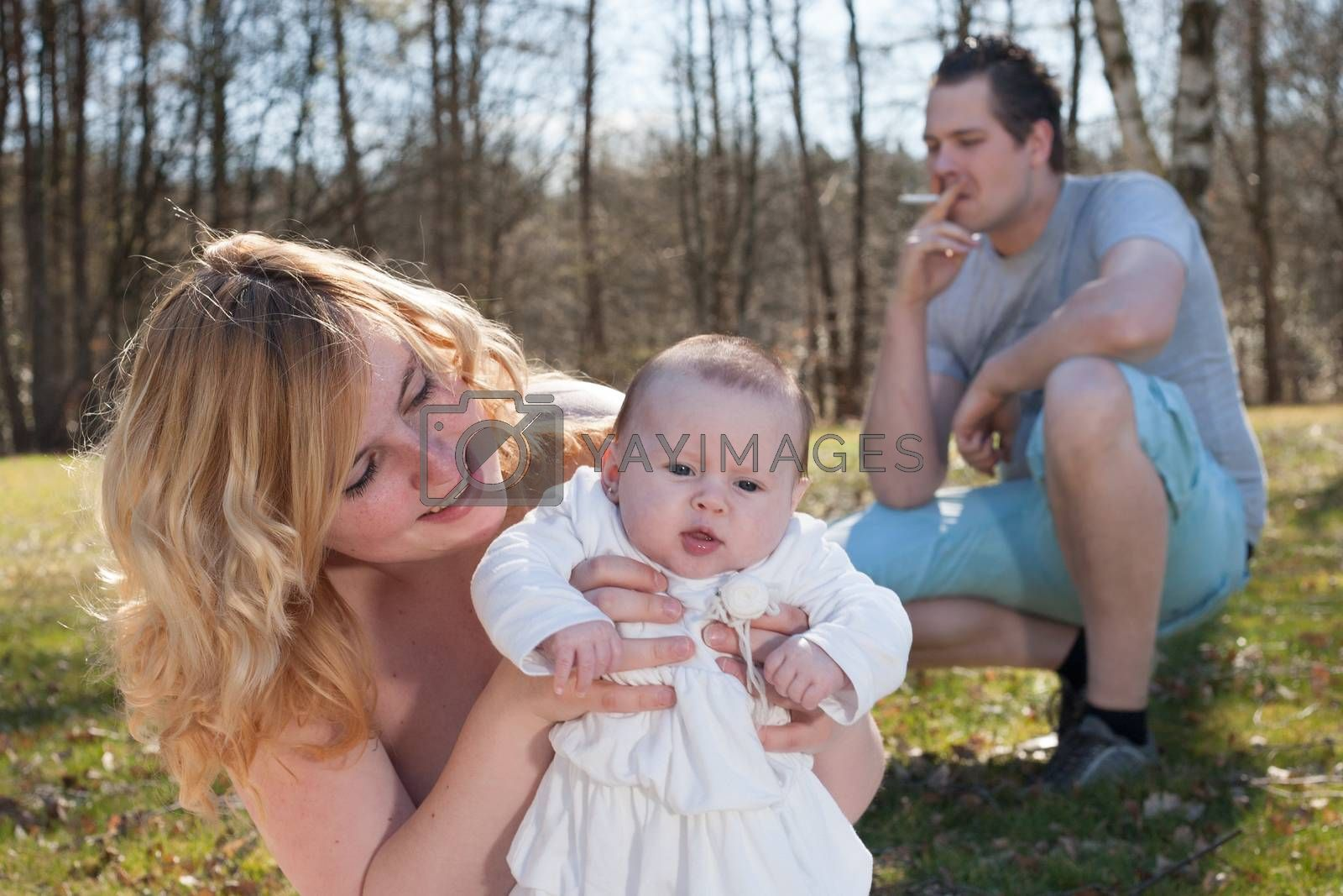 Young father is smoking while its unhealthy for his family. Distance between father and family