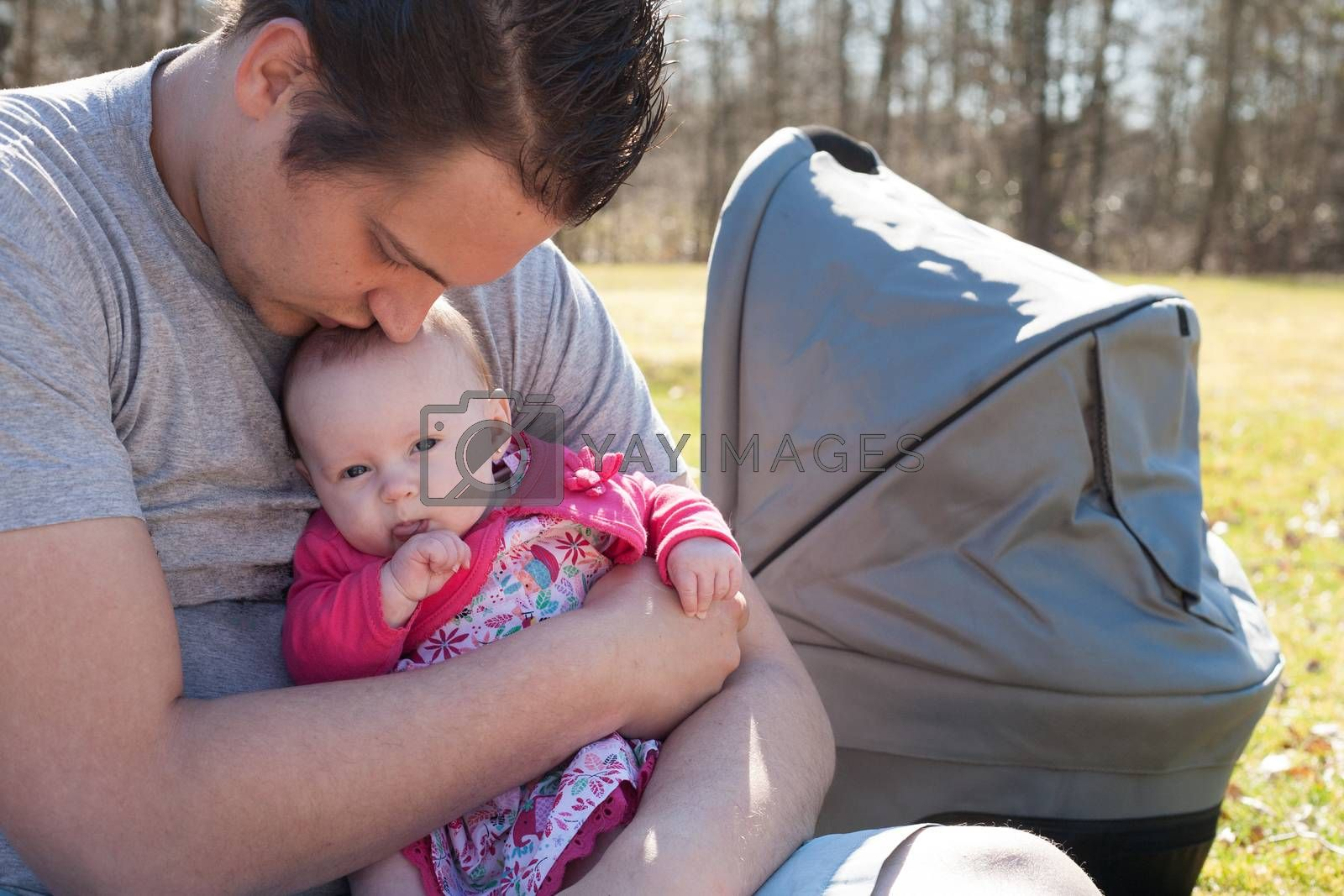 Young father is having some nice time with his baby on a sunny day