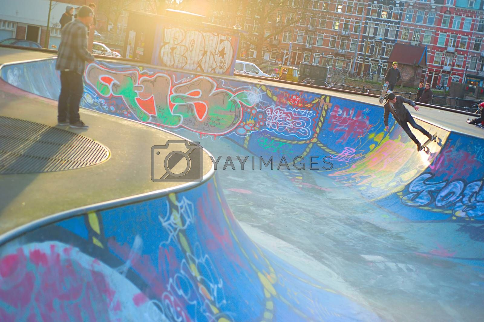 AMSTERDAM, THE NETHERLANDS ��� FEBRUARY 24, 2014: Local skaters are training on a skate ground in Amsterdam on a warm winter day. Residential districts are well equipped for sport activities there.