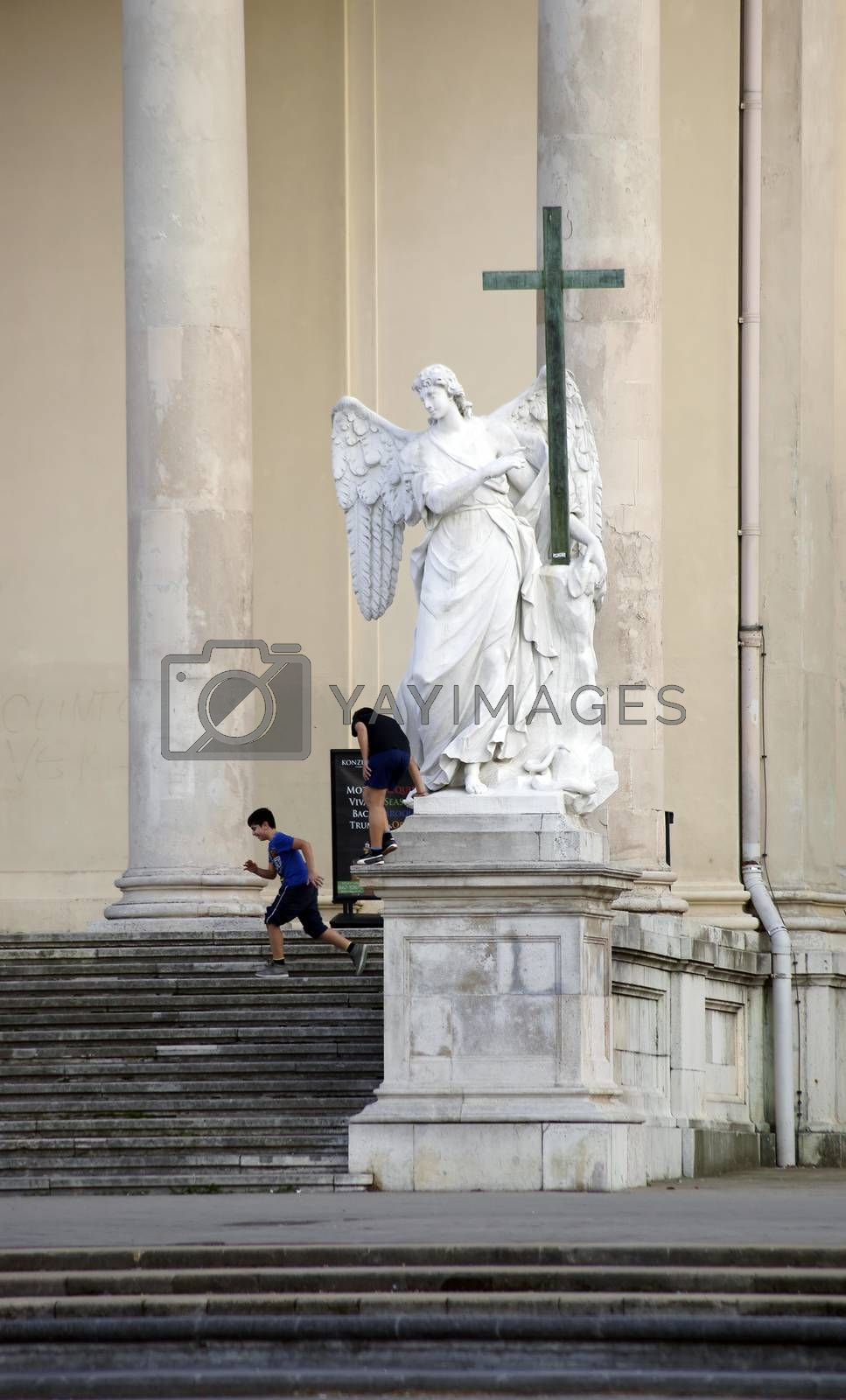Vienna, Austria - March 30, 2014: Children play on the stairs of the entrance of the St. Charles Church on an angel sculpture on March 30, 2014 in Vienna.