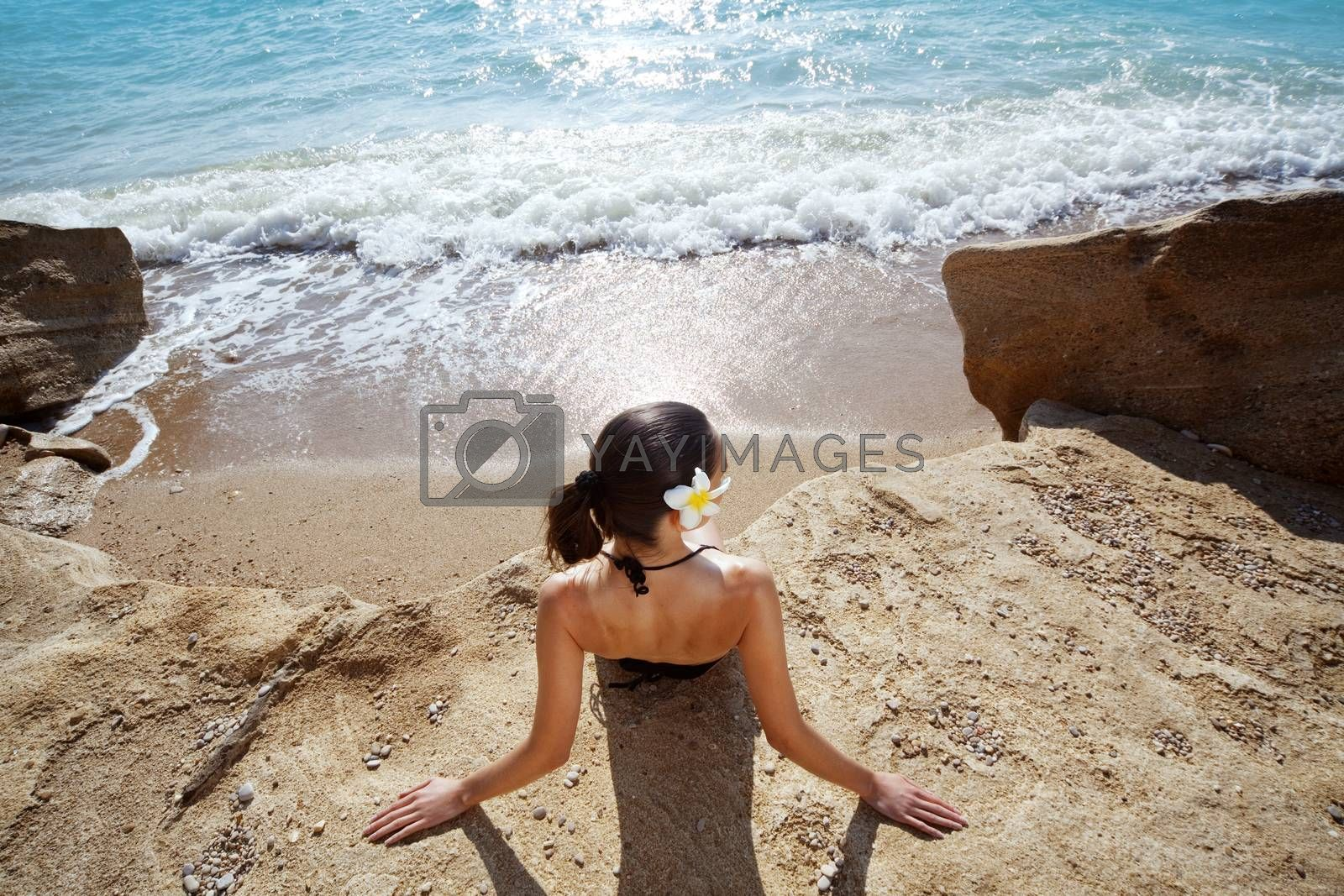 Closeup portrait of beautiful young woman with golden tan resting at beach in summer