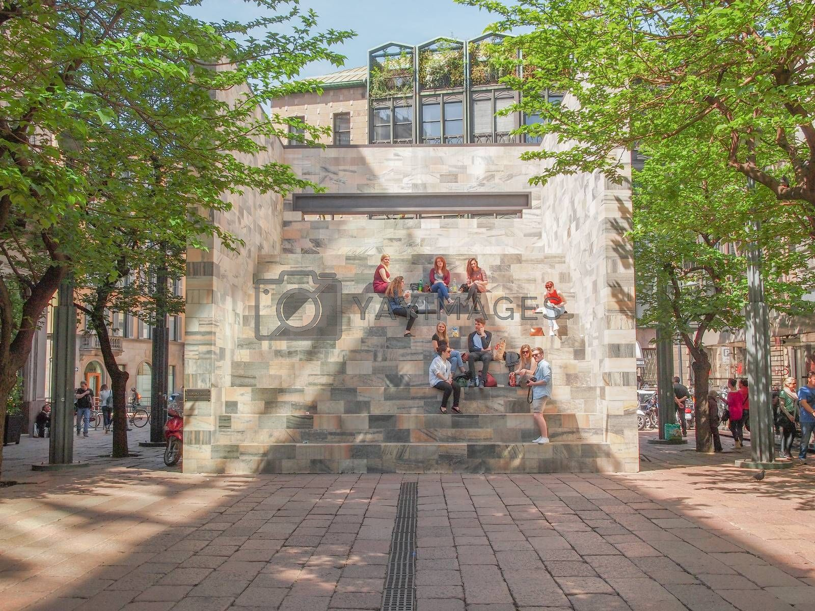 MILAN, ITALY - APRIL 10, 2014: People seated on the stairway of the Sandro Pertini monument in Milan dedicated to the former Italian President designed by architect Aldo Rossi in 1988