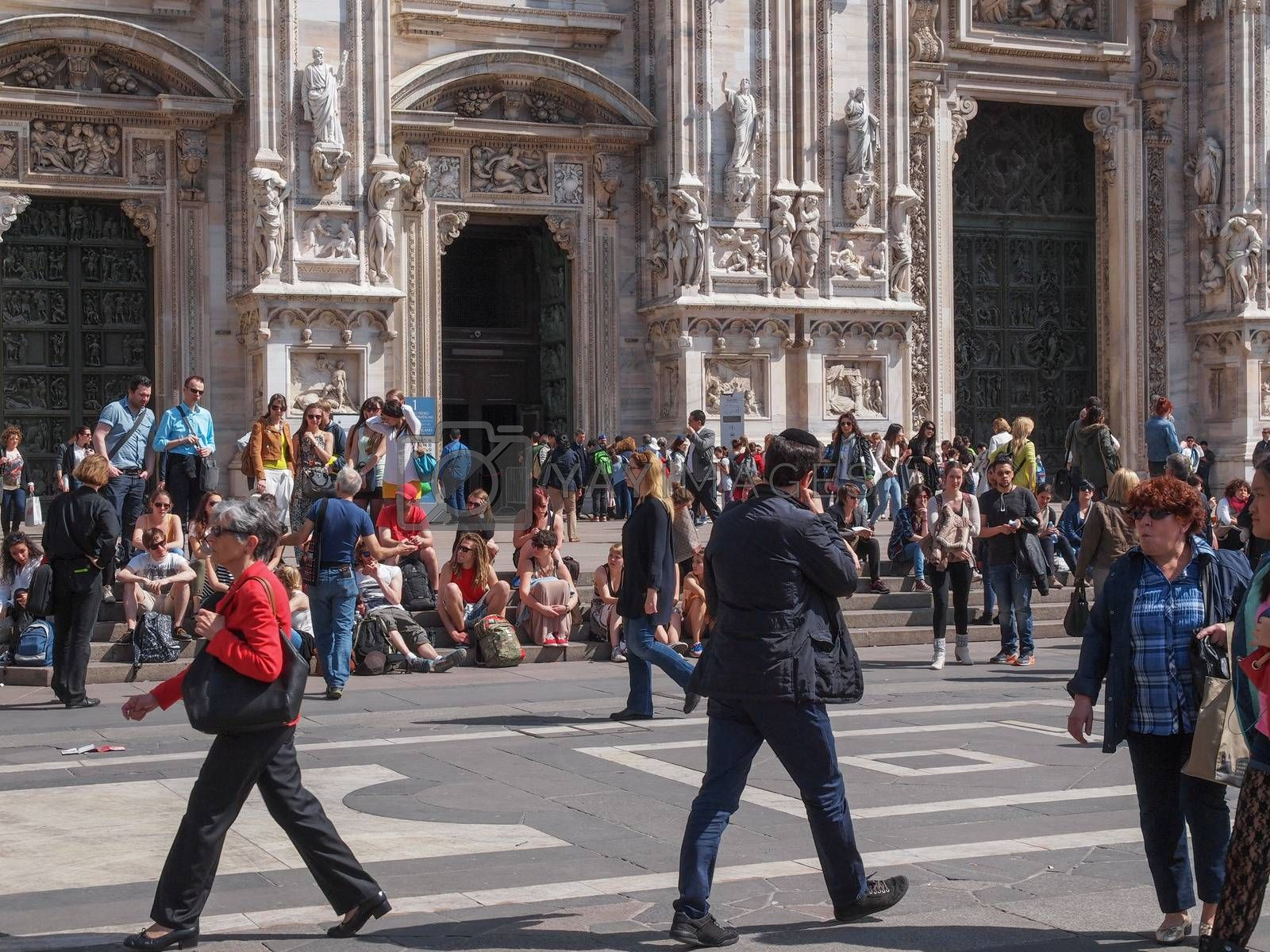 MILAN, ITALY - APRIL 10, 2014: Tourists visiting the Piazza Duomo square in Milan Italy