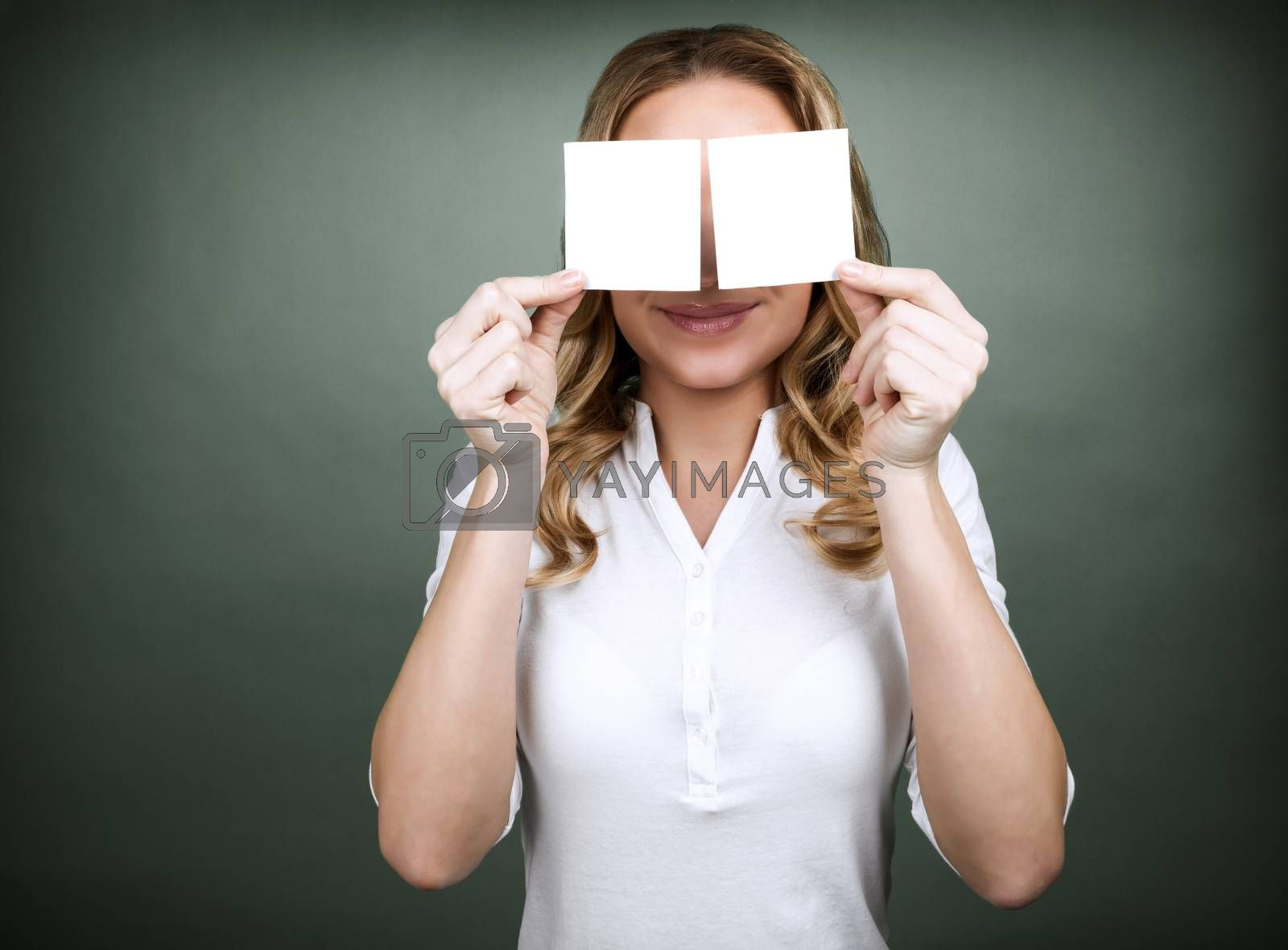 Portrait of cute blond girl closes her eyes with two blank cards isolated on grey background, copy space, place for advertisement
