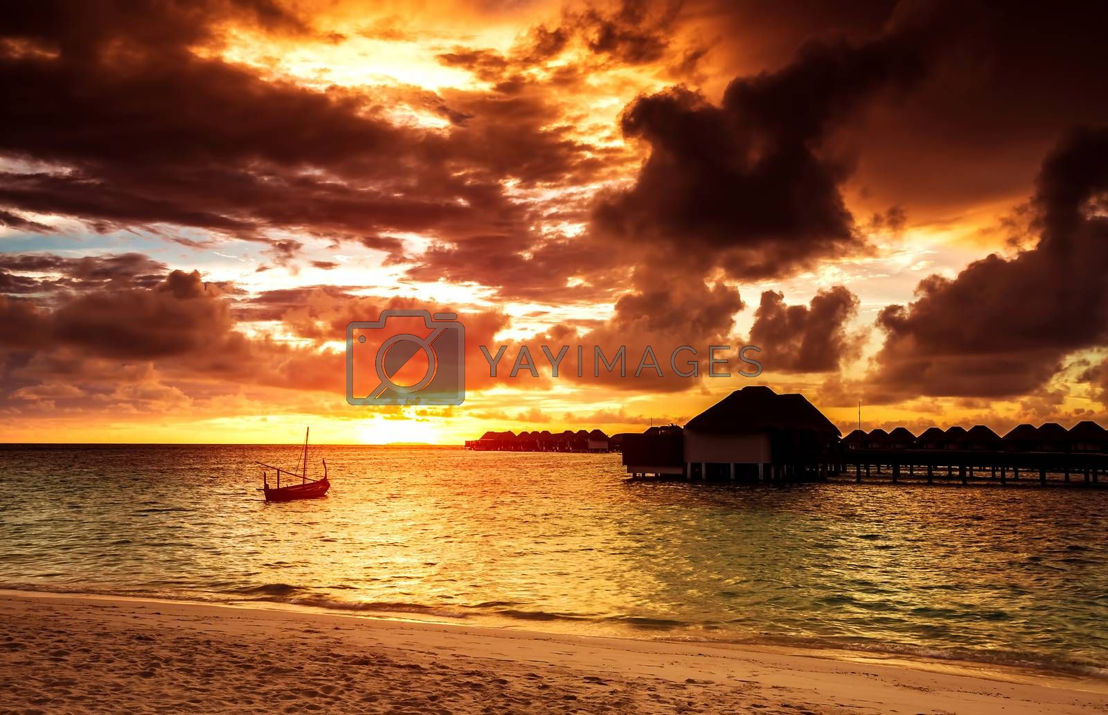 Overcast weather over sea, beautiful seascape in the evening in orange sunset light, summer holidays on Maldives island, travel and tourism concept