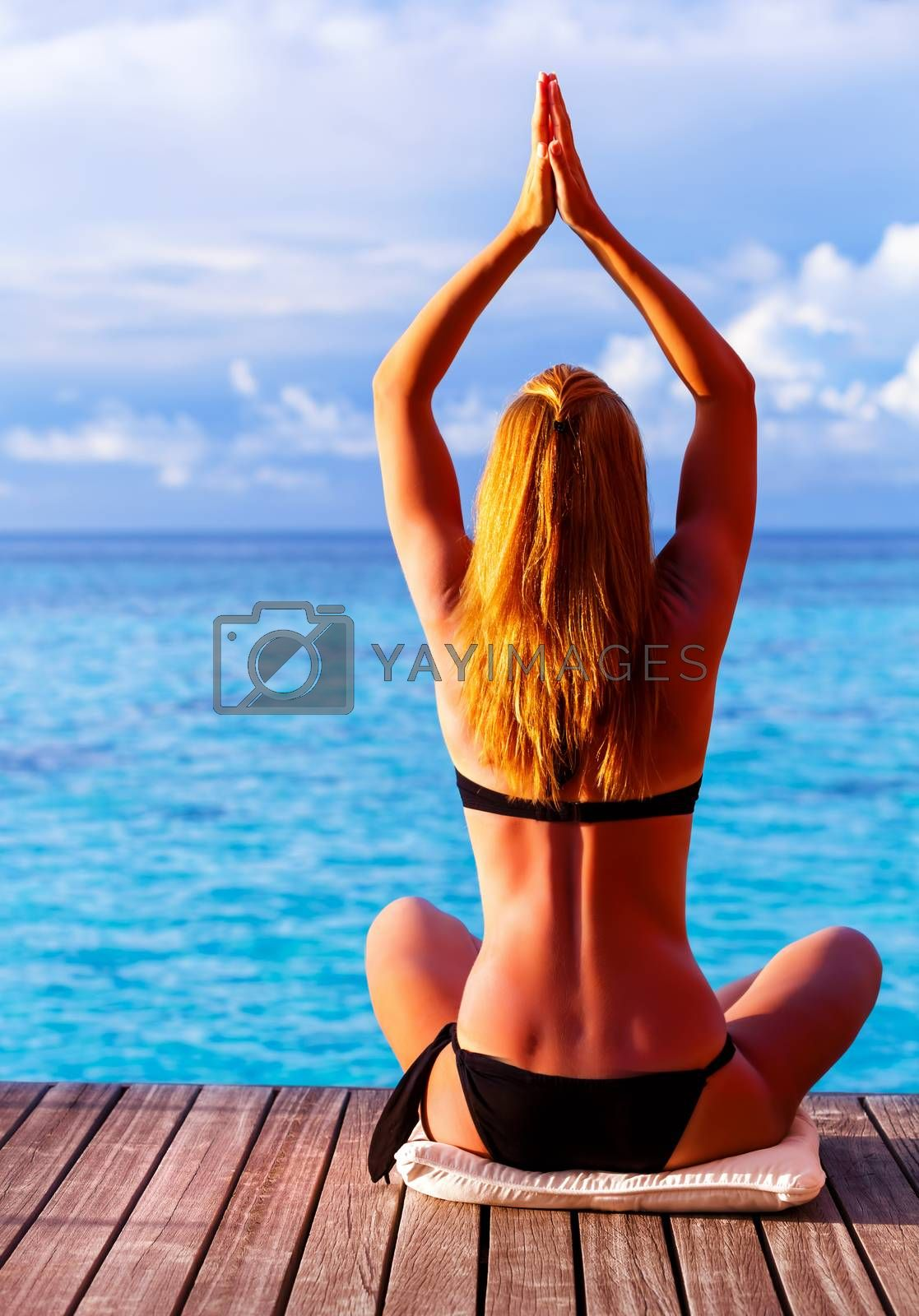 Rear view of sexy female doing yoga outdoors in warm sun light near the sea, phisical exercise for clearing mind, healthy lifestyle, peace and harmony concept