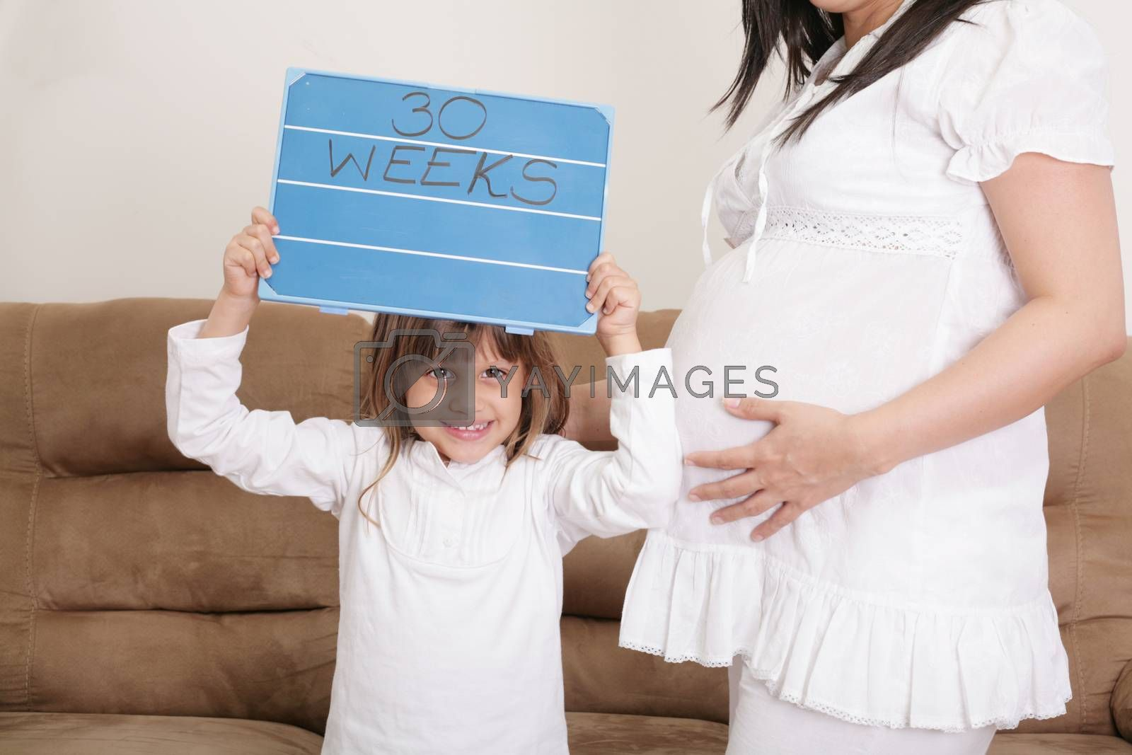 Royalty free image of Girl holding a 30 weeks sign to her expectant mother by dacasdo