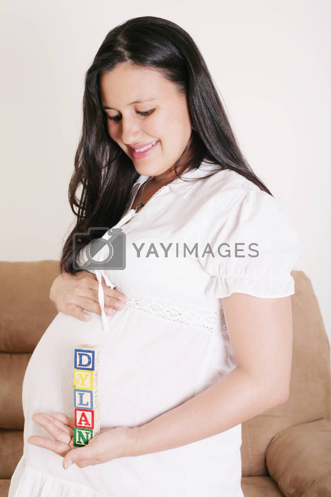 Royalty free image of Close up of a pregnant woman with baby letters on her hand by dacasdo