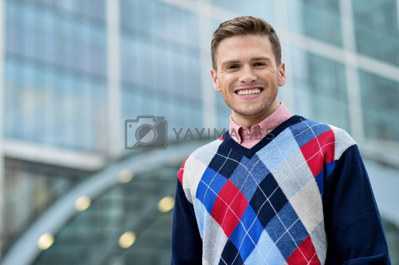 Royalty free image of Young man standing outside modern building by stockyimages