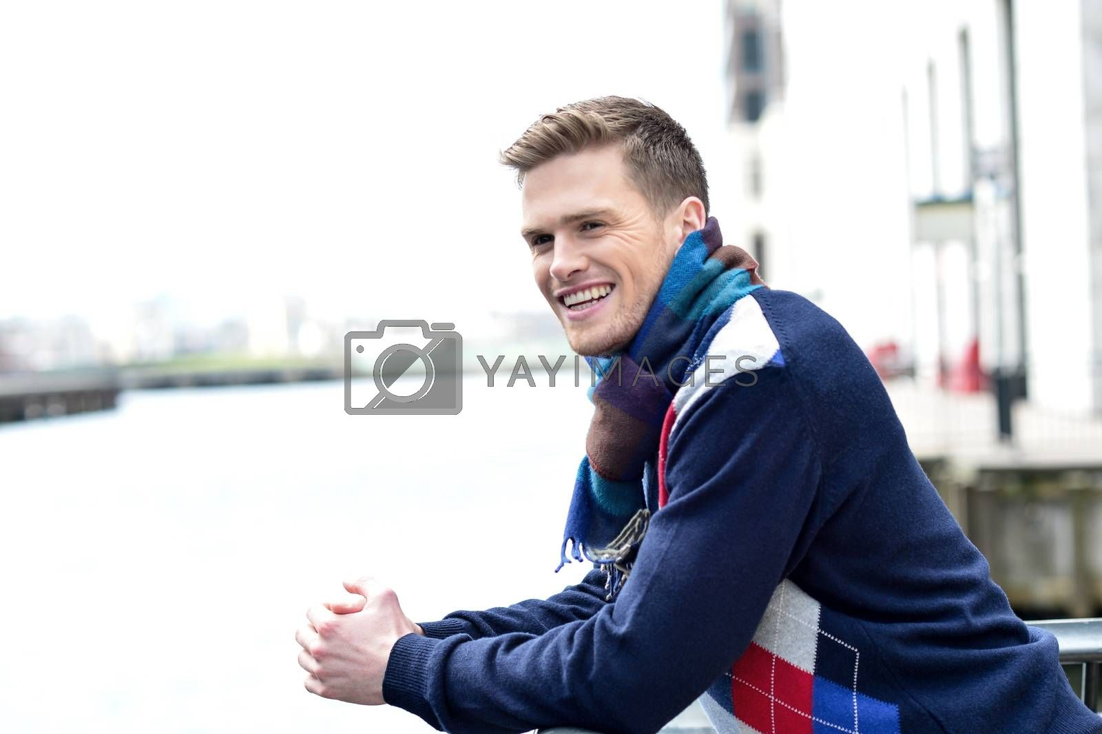 Royalty free image of Handsome man leaning on railing at river by stockyimages