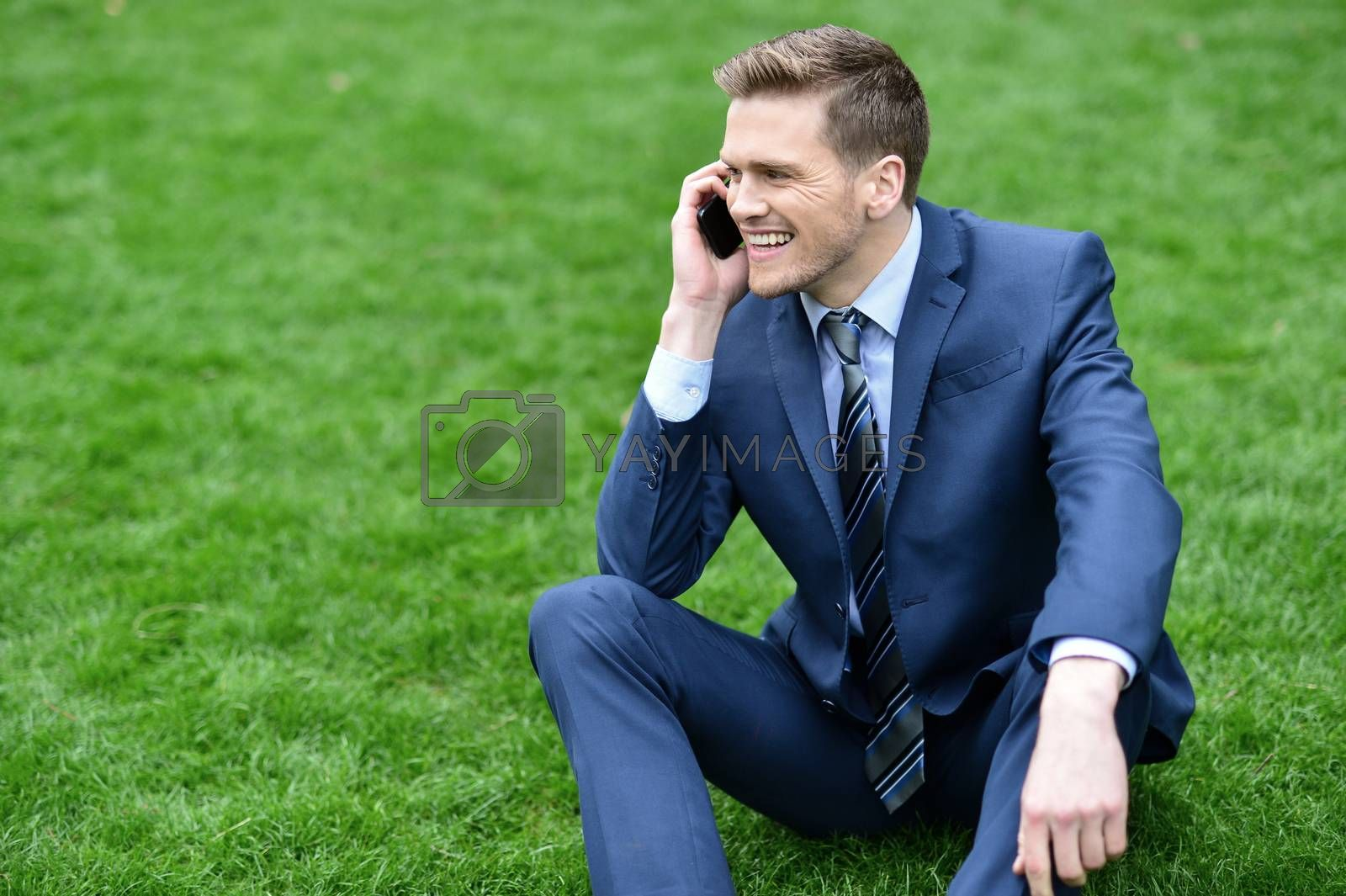 Royalty free image of Businessman using mobile phone in park by stockyimages