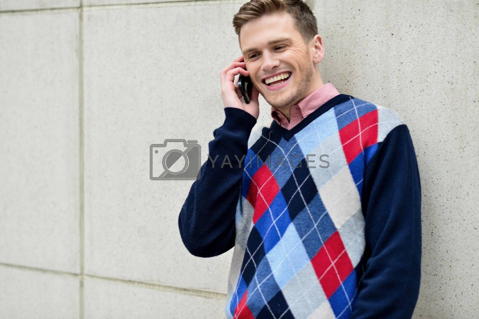 Royalty free image of Happy man leaning against wall with cell phone by stockyimages