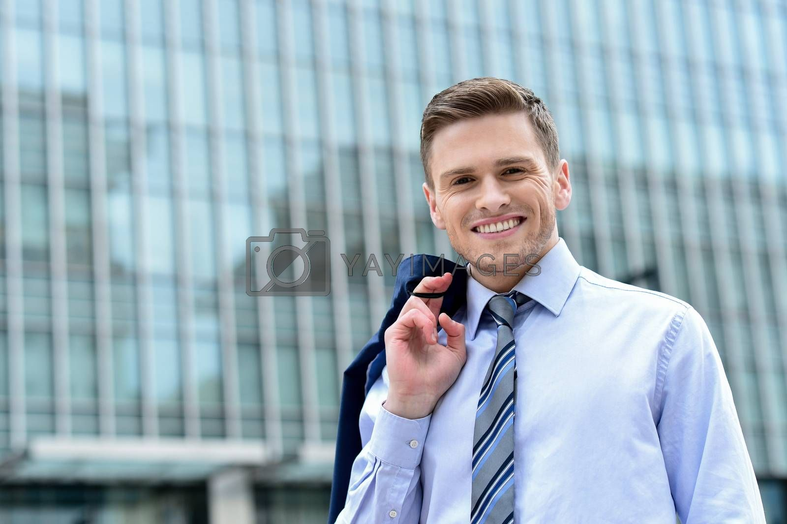 Businessman standing outside modern building by stockyimages