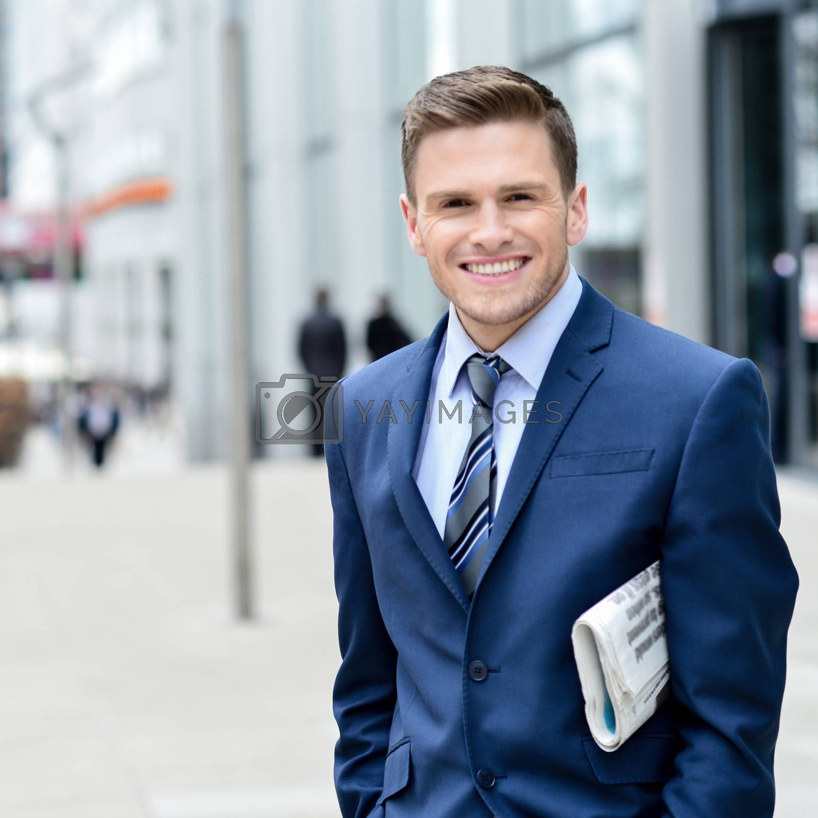 Smiling satisfied businessman holding news paper at outdoor