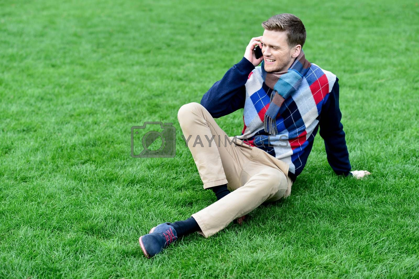 Happy young man using mobile phone on park by stockyimages