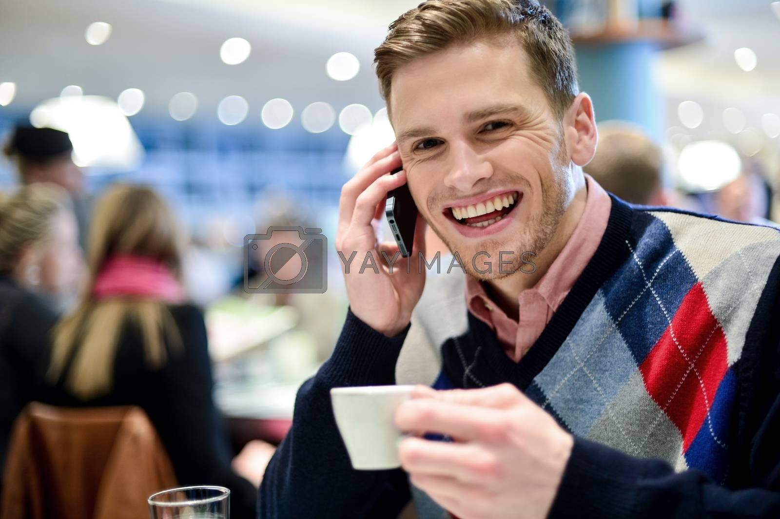 Royalty free image of Young man using mobile phone in cafe by stockyimages