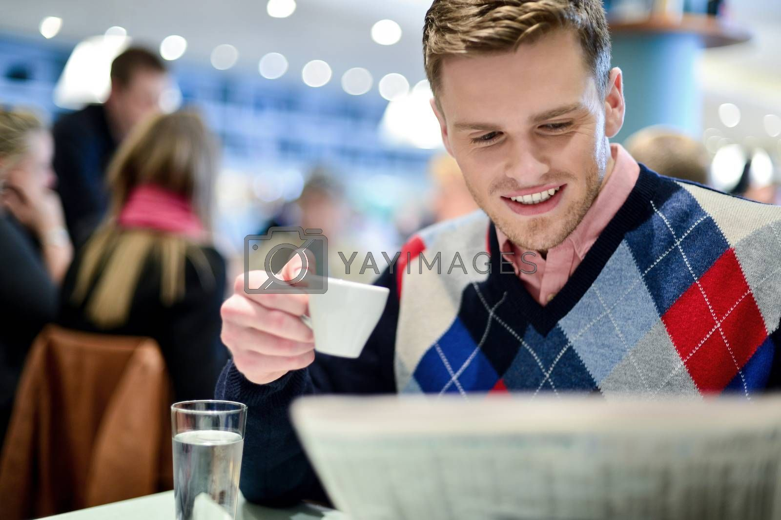 Royalty free image of Man reading newspaper at outdoor cafe by stockyimages