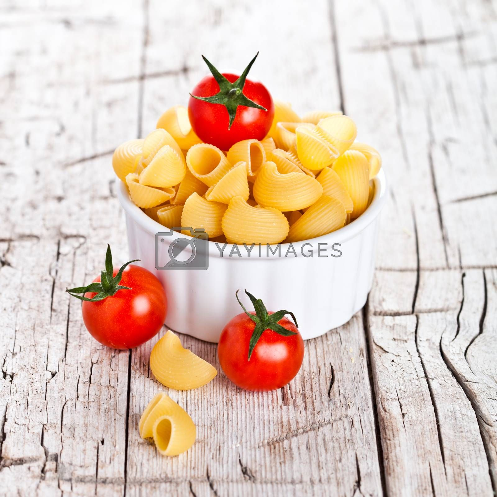 Royalty free image of uncooked pasta and cherry tomatoes in a bowl by marylooo