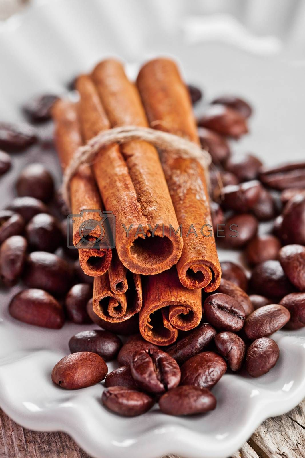Royalty free image of stack of cinnamon sticks and coffee beans by marylooo