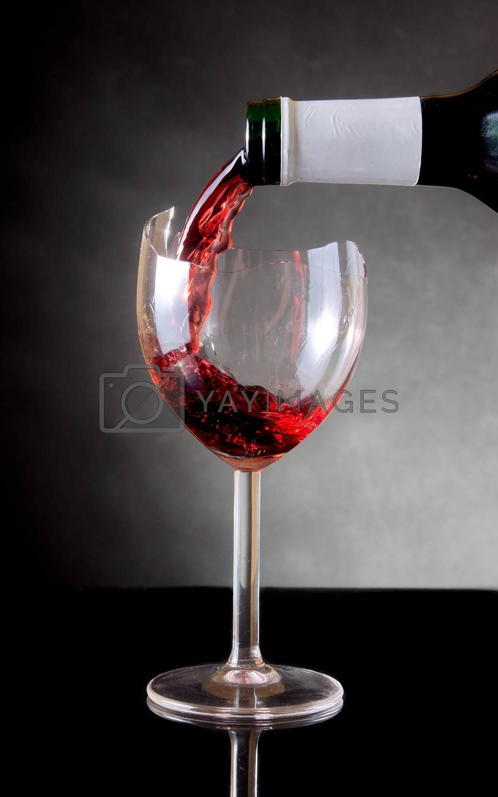 Pouring red vine into a broken glass by anderm