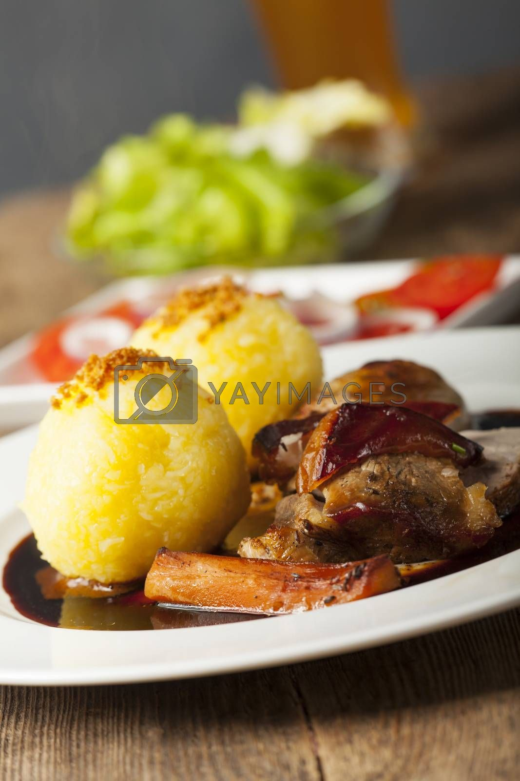 Royalty free image of roasted pork dish with dumplings  by bernjuer