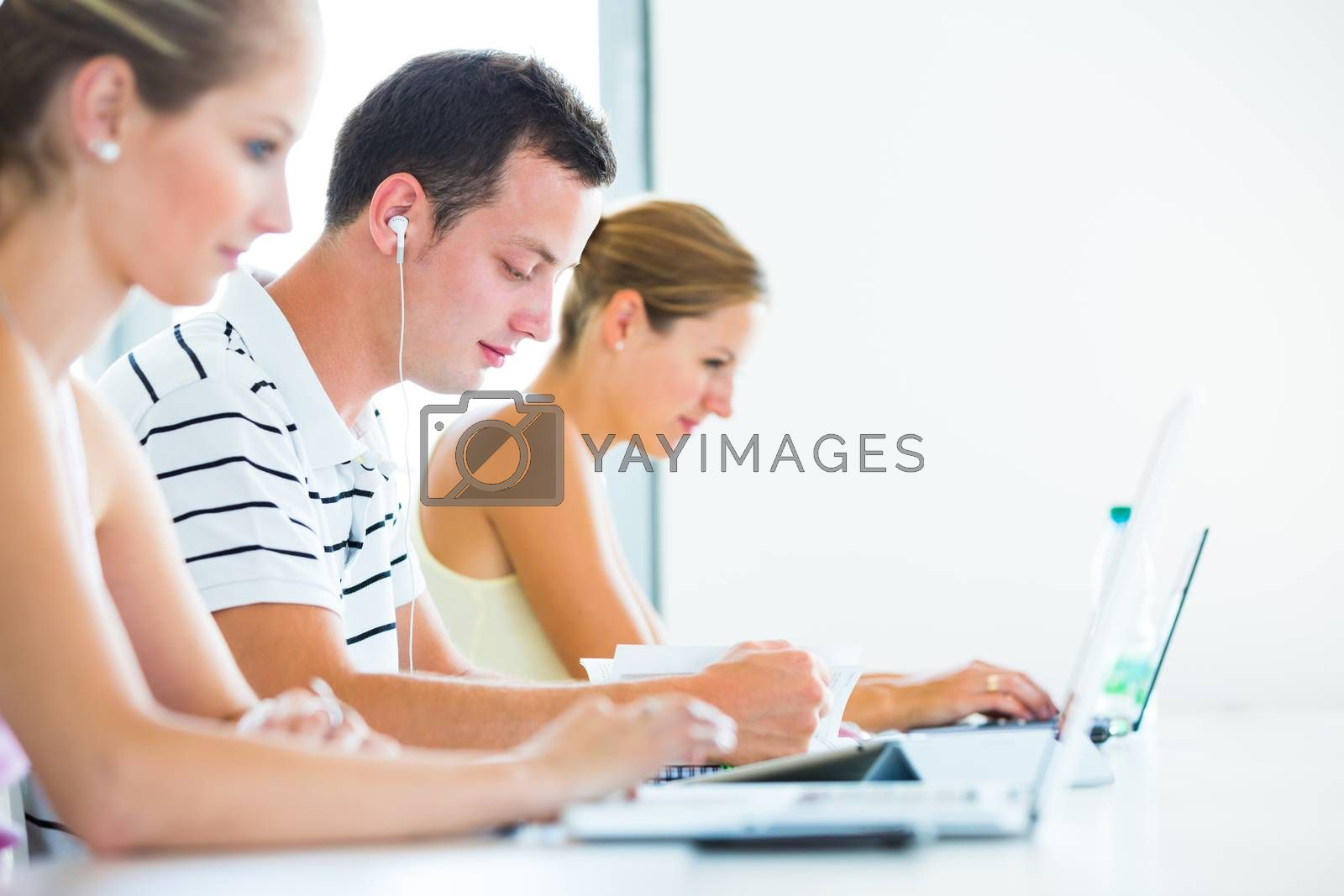 Royalty free image of On campus - pretty, female student with books and laptop by viktor_cap