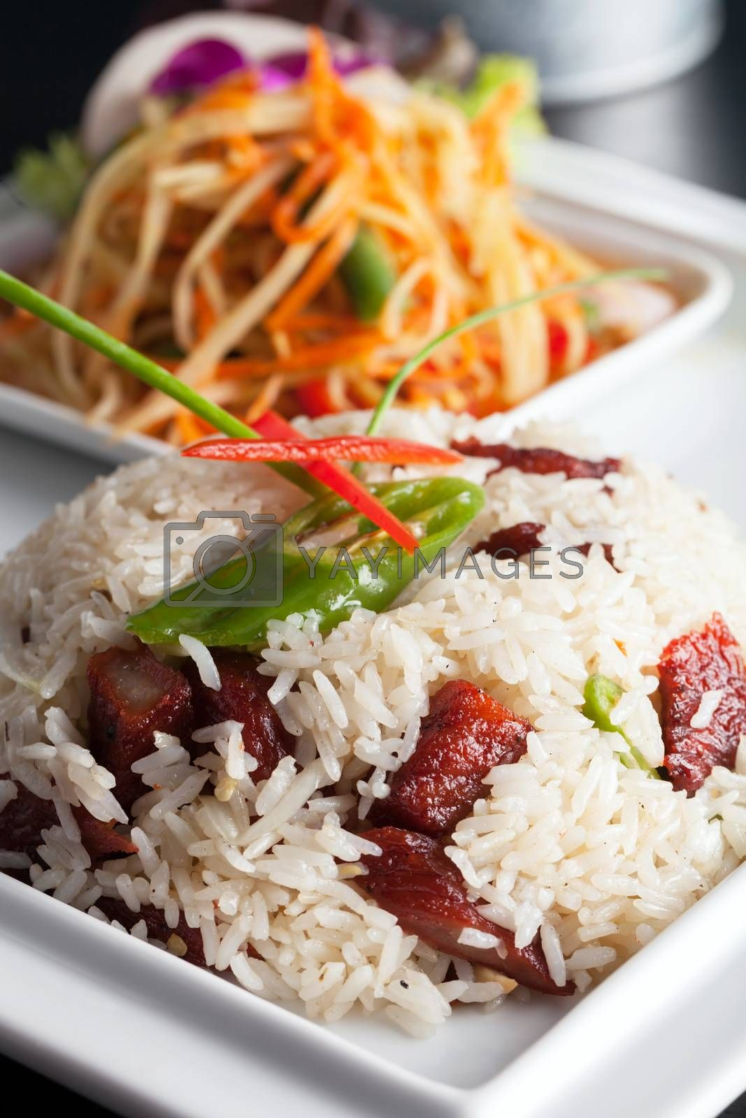 Royalty free image of Thai Pork and Rice with Som Tum Salad by graficallyminded
