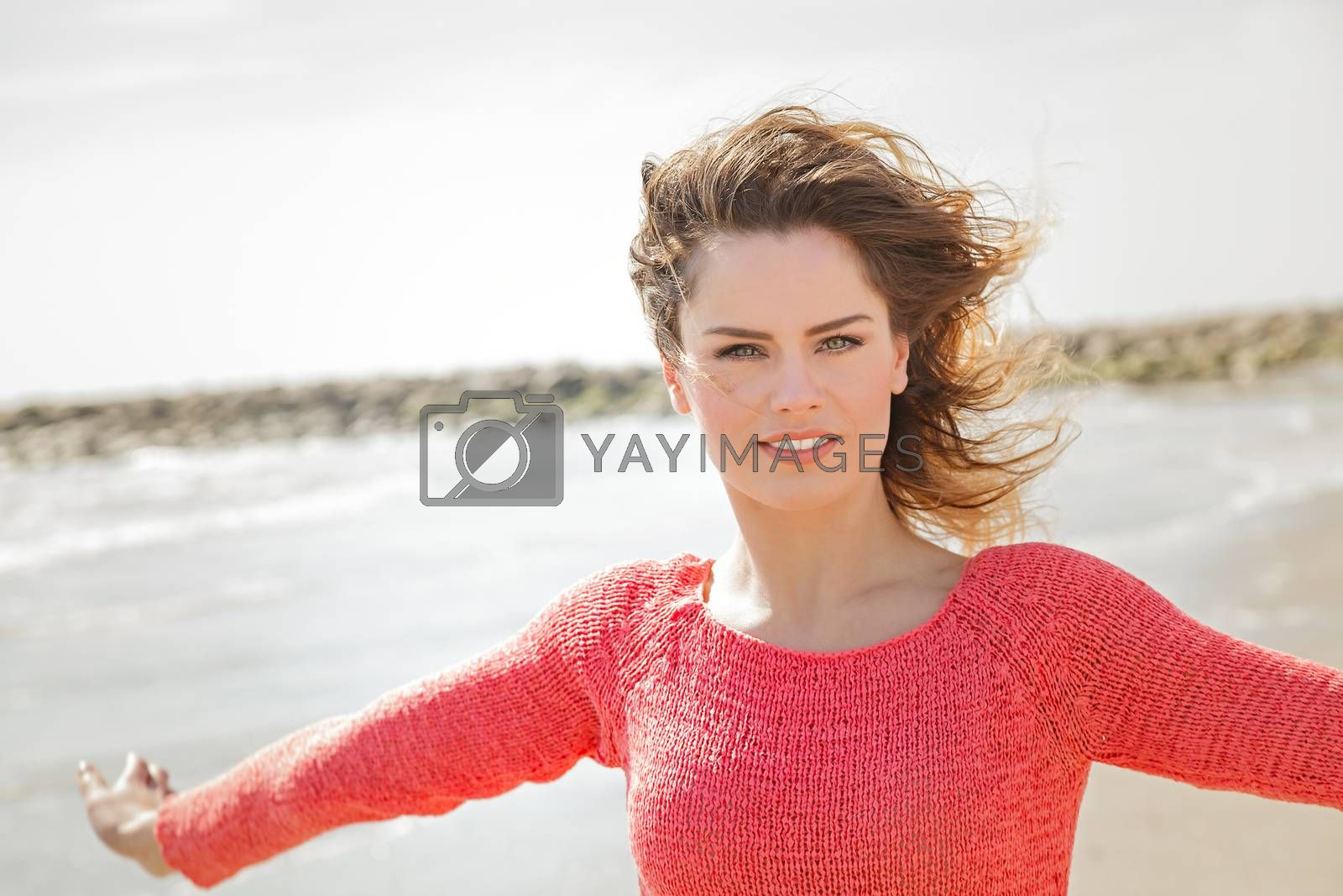 Royalty free image of Beautiful young woman smiling on a windy day at the seaside by alessandroguerriero