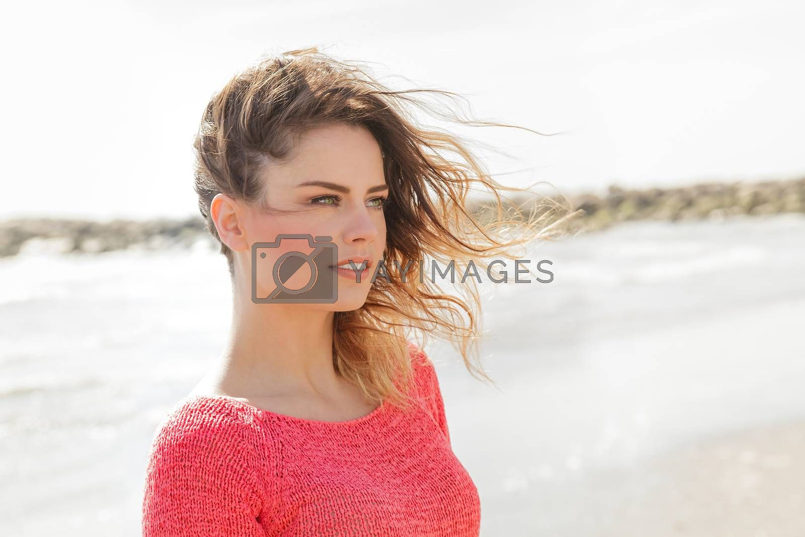Royalty free image of Beautiful young girl looking aside on the beach by alessandroguerriero