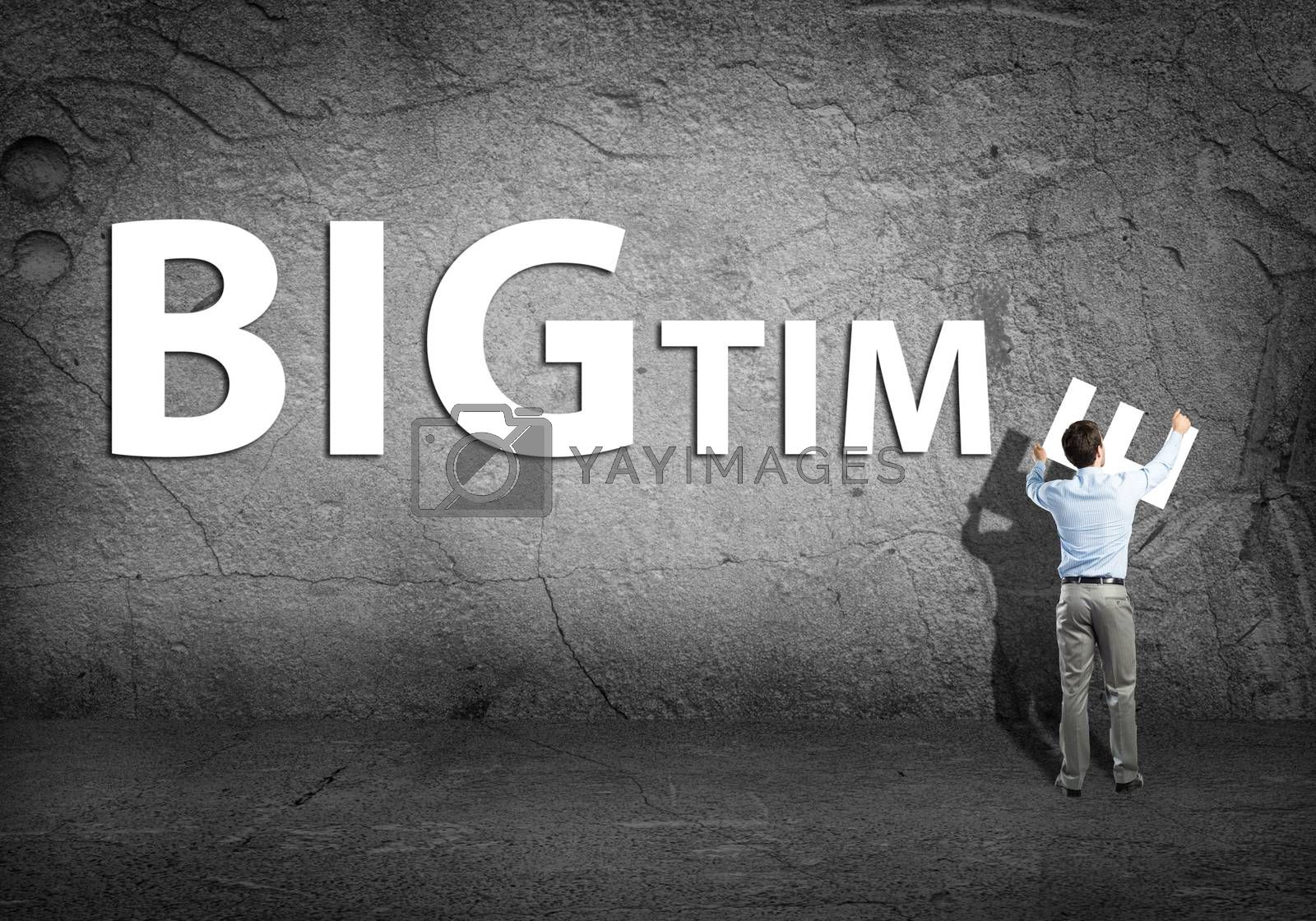 Royalty free image of young businessman adds bigtime word by adam121