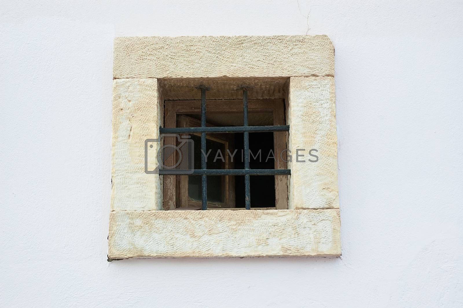 Old open window on white shabby wall with bars