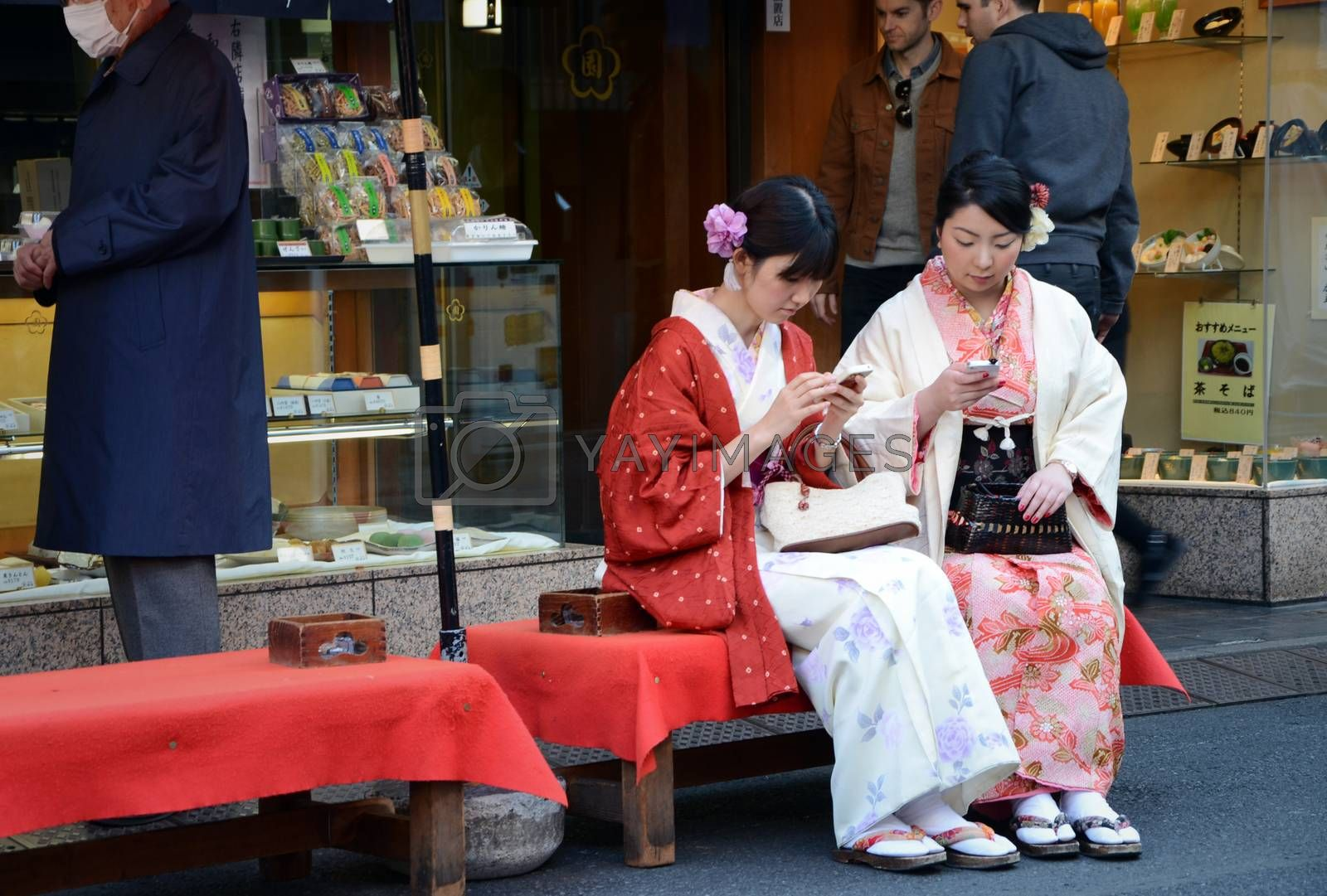 TOKYO, JAPAN - NOVEMBER 21, 2013: Young Japanese women wearing a traditional dress called Kimono for cherry (Sakura) blossom viewing at Asakusa area in Tokyo on November 21, 2013.