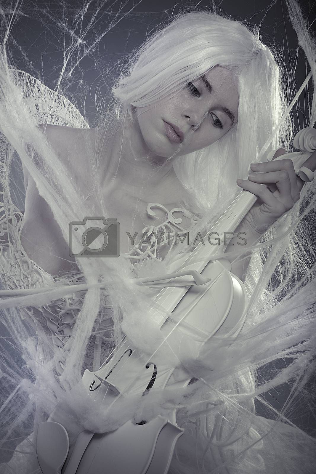 Sexy beautiful woman trapped in a spider web with a white violin, lace dress