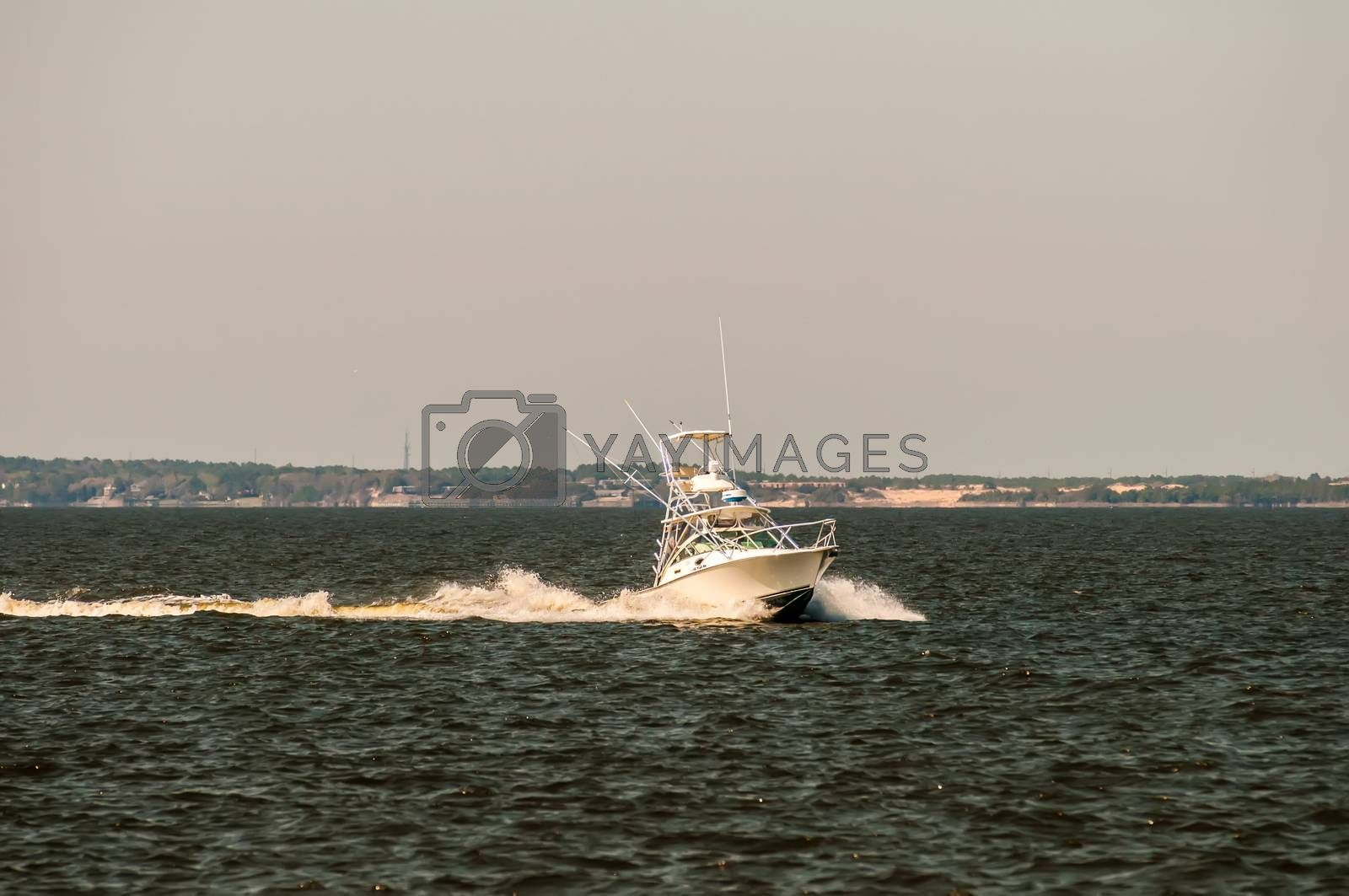 moving fishing power boat in a distance on the ocean