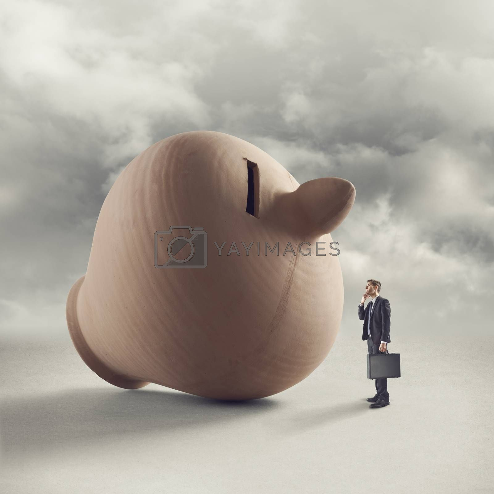 Businessman with briefcase contemplating a huge clay coin bank with sky on background.
