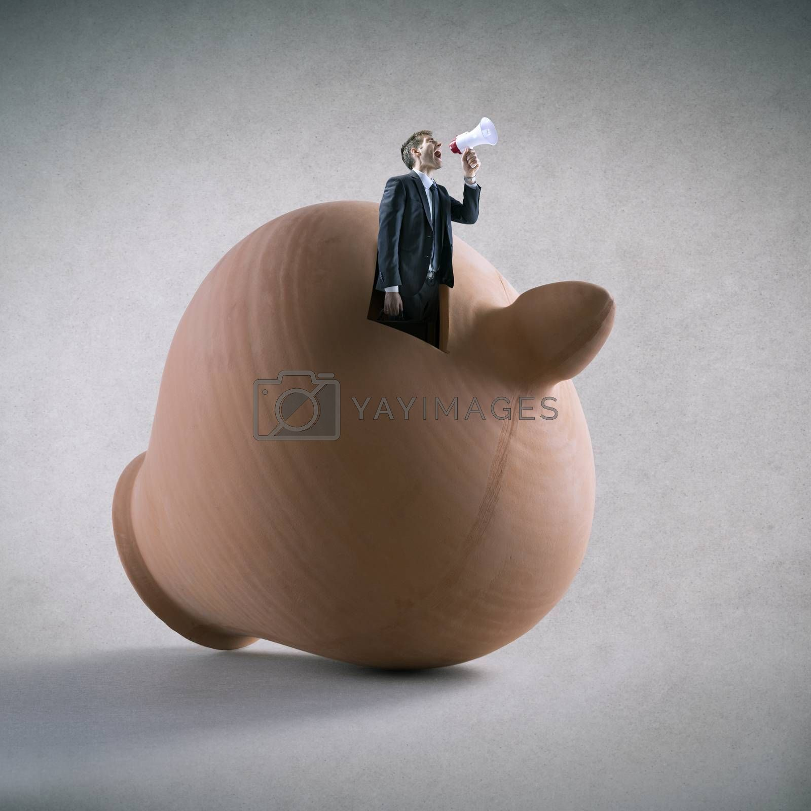 Businessman yelling through megaphone emerging from a clay coin bank.